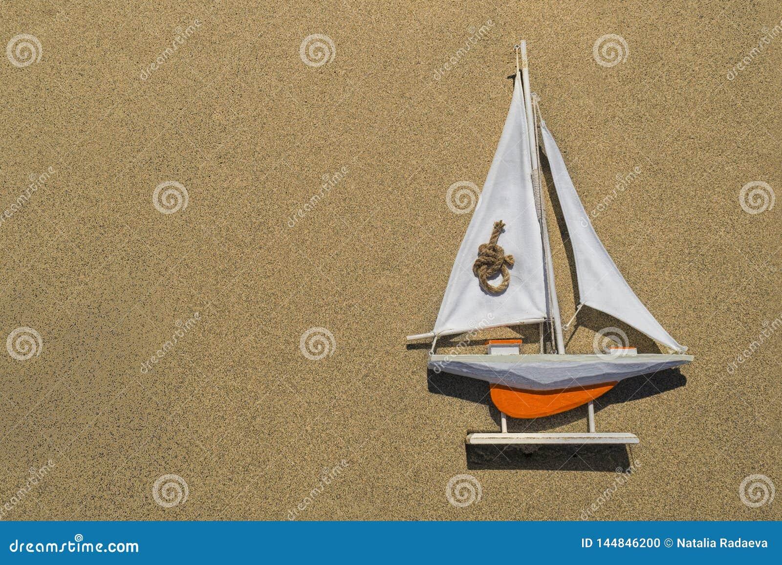 Een stuk speelgoed oranje schip met een wit zeil ligt op het geweven zand op het recht