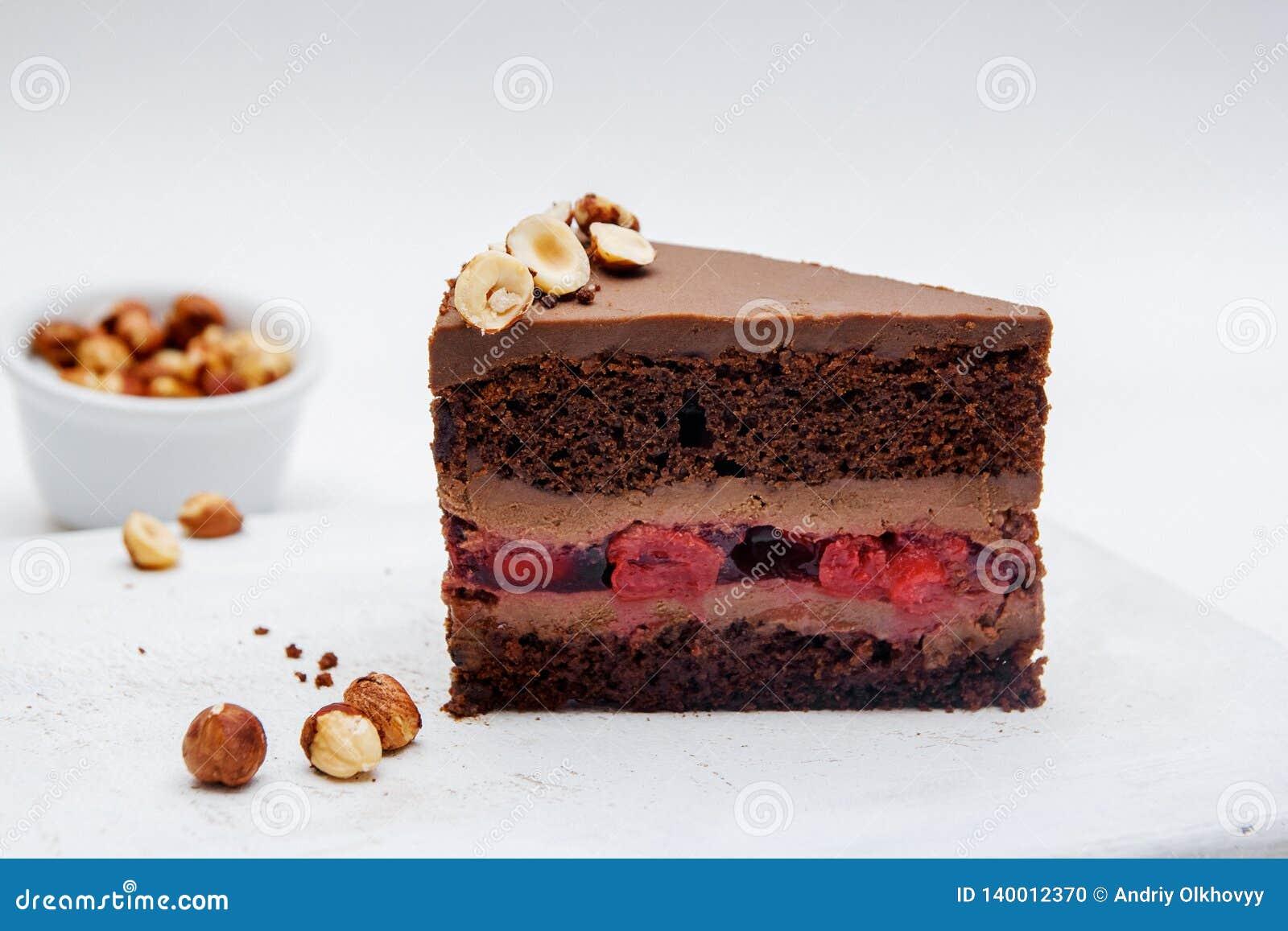 Een stuk van chocoladecake met kersen en hazelnoot op witte achtergrond Heerlijke chocoladecakes op lijstclose-up