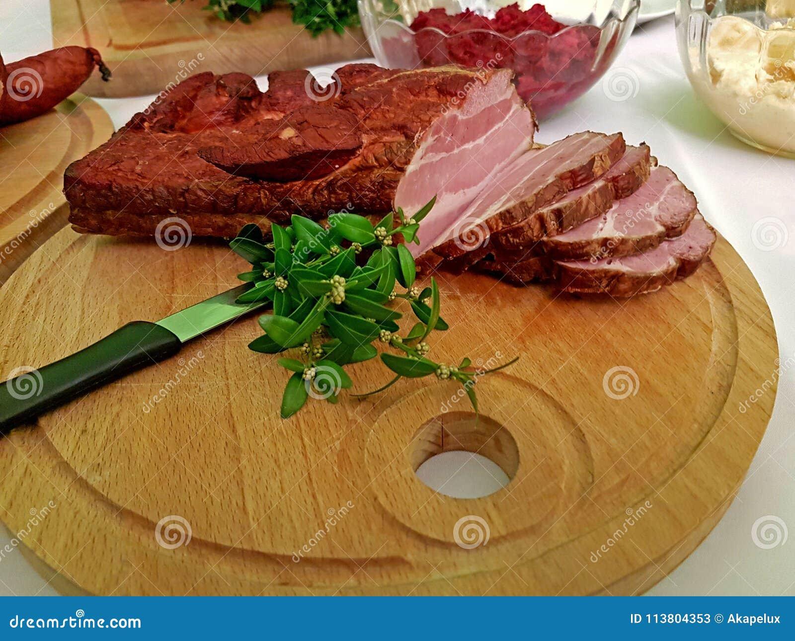 Een stuk van gerookte spons hakte op een houten die raad met een groene installatie wordt verfraaid Vet high-protein hoog-calorie