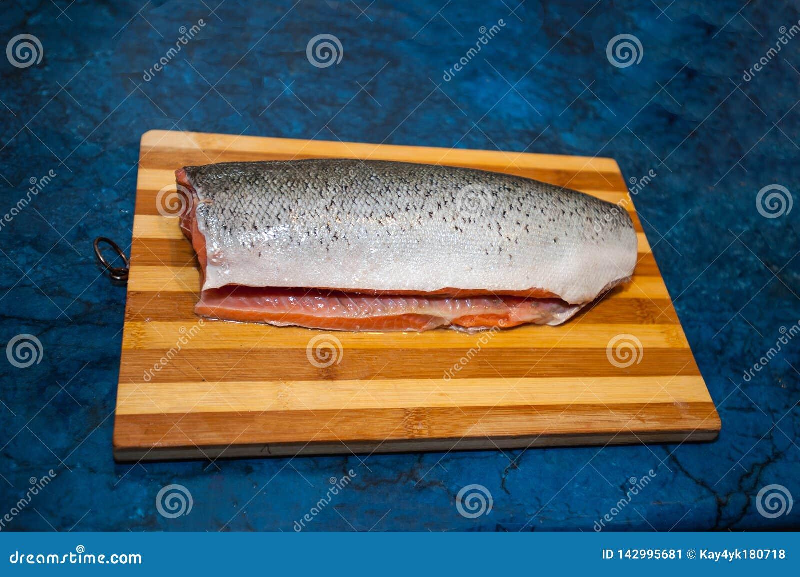 Een stuk verse, ruwe, rode vissen op een houten bruine scherpe raad, op een zwarte achtergrond Mooie zalmfilet die ligt