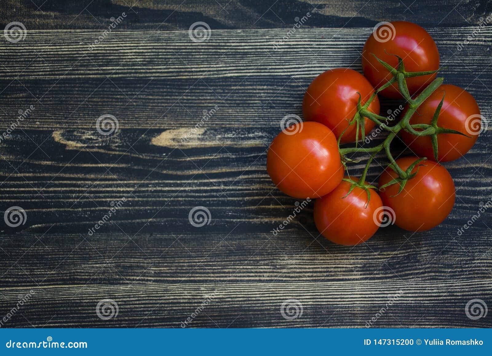 Een tak van verse rode tomaten op een zwarte achtergrond