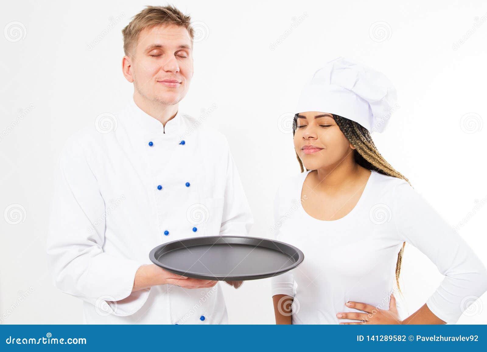 Een team van chef-koks snuift het prettige aroma van iets op een leeg die dienblad op wit wordt geïsoleerd
