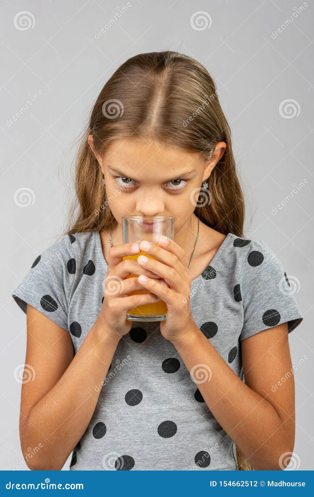 Een tien éénjarigenmeisje drinkt sap en geniet van de geur