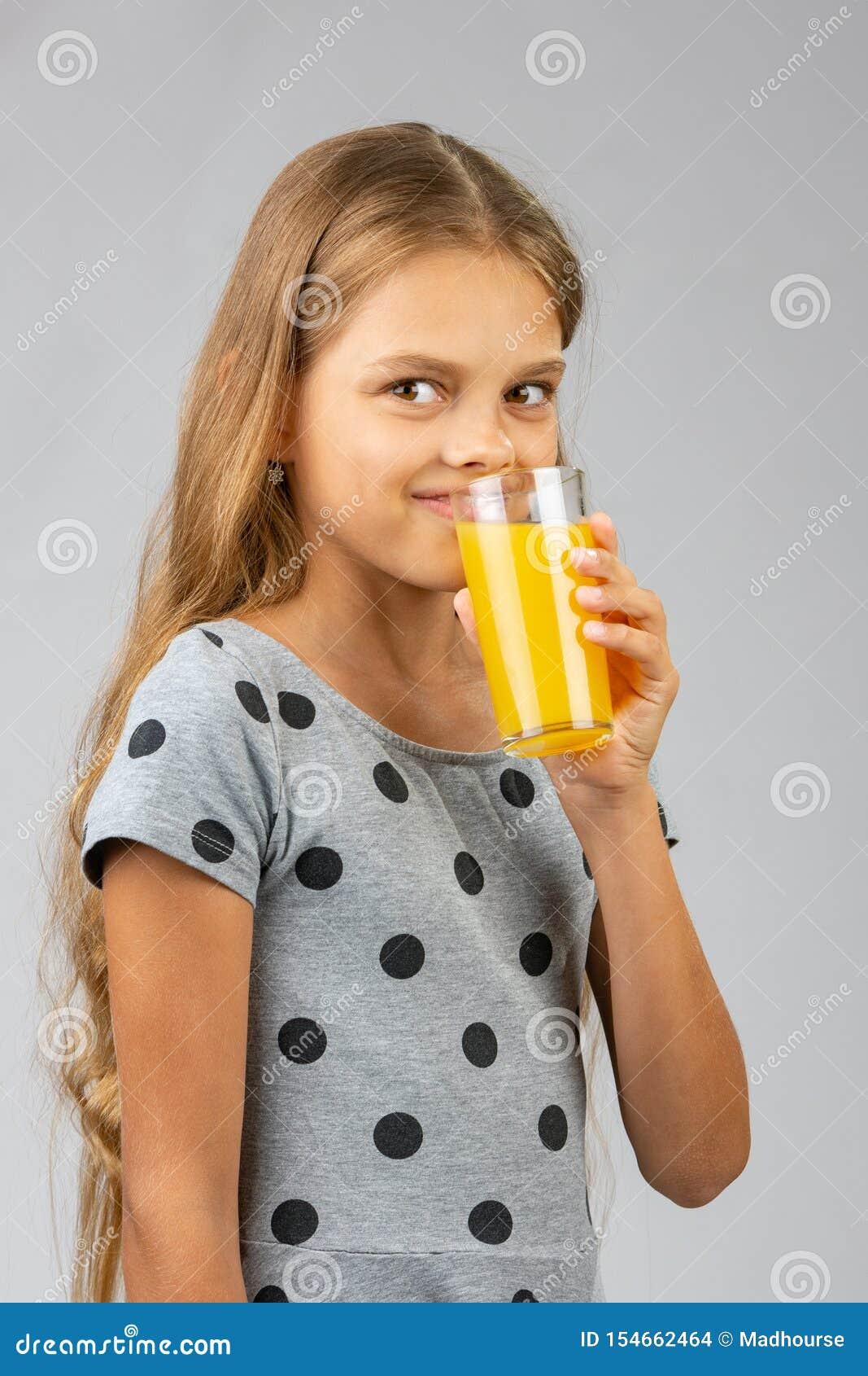 Een tien-jaar-oud meisje drinkt sap, en met een glimlach bekeek het kader