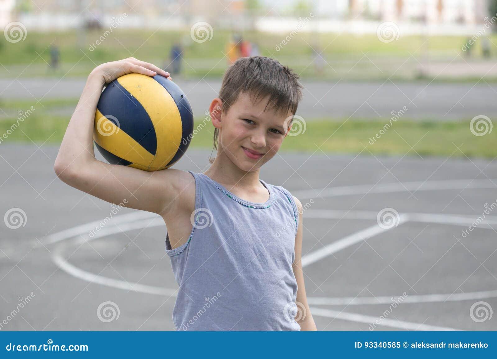 Een tiener in een vest houdt een bal in zijn hand