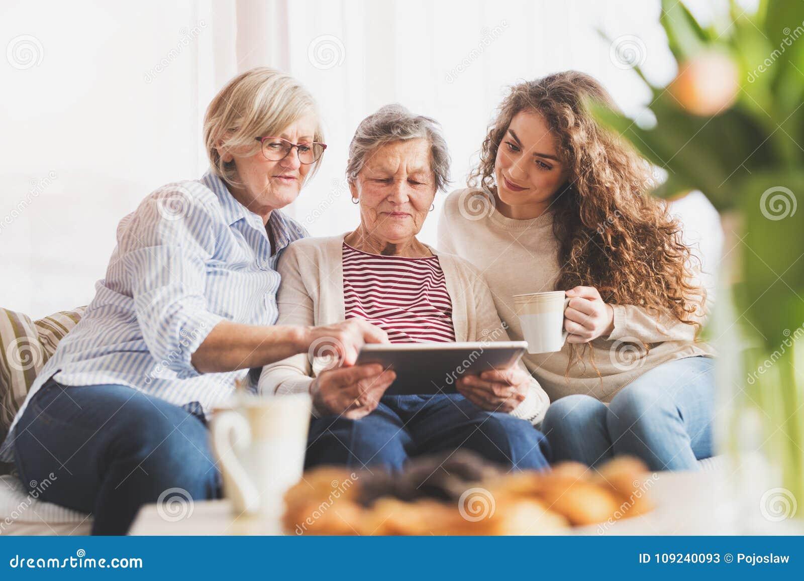 Een tiener, een moeder en een grootmoeder met tablet thuis