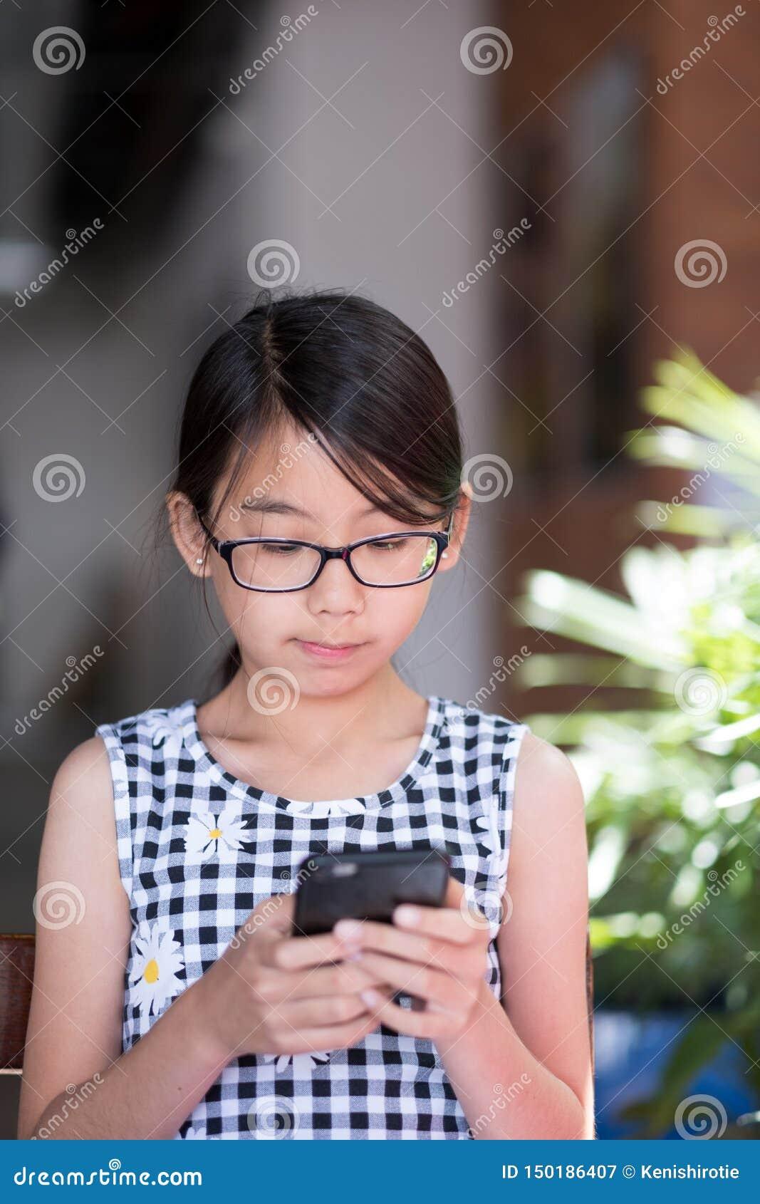 Een tienermeisje die smartphone in koffie met behulp van