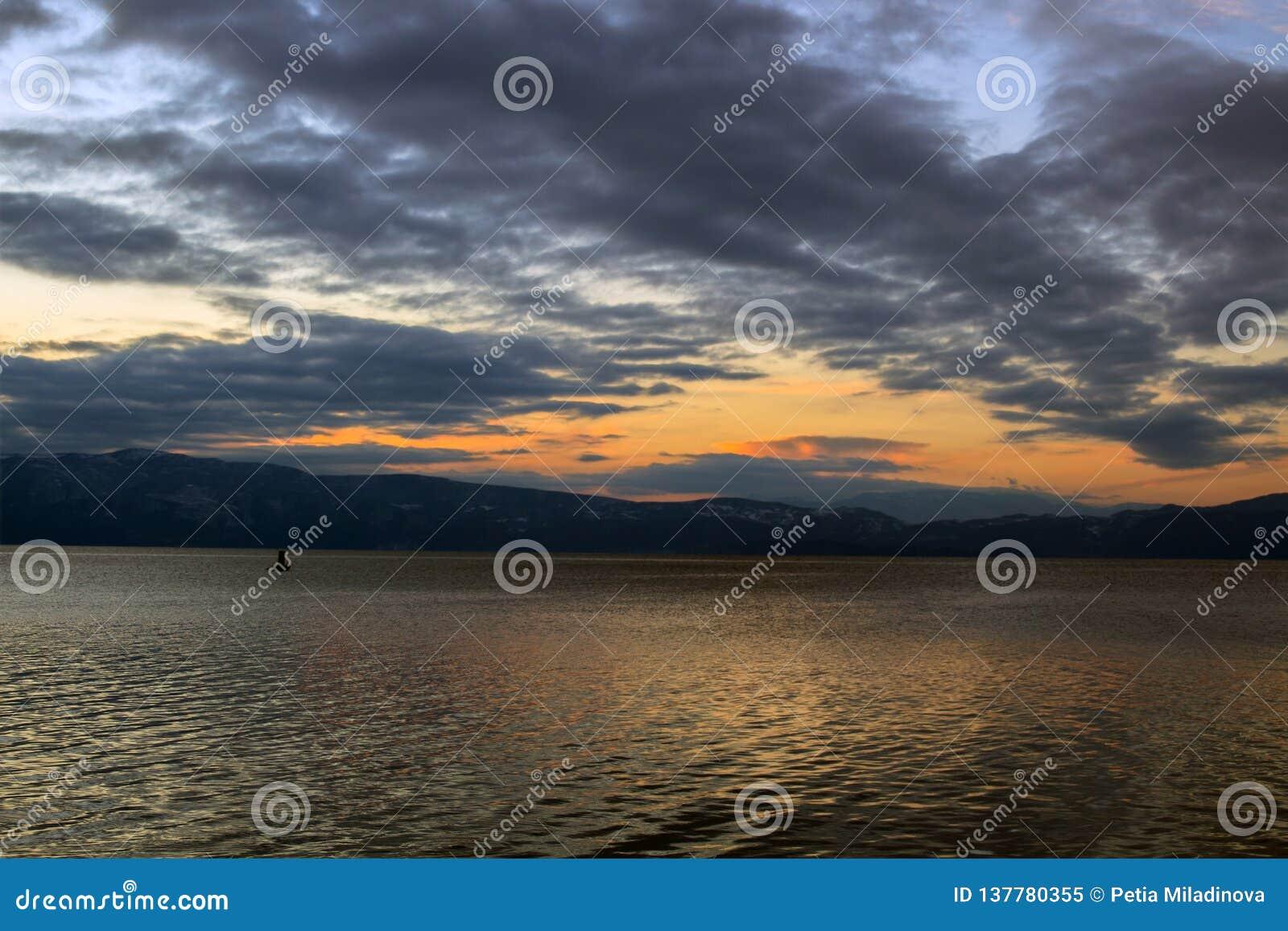 Een toneelzonsondergang met een zwarte wolk boven de laatste zonneschijn dacht in Ohrid-Meer, Macedonië na