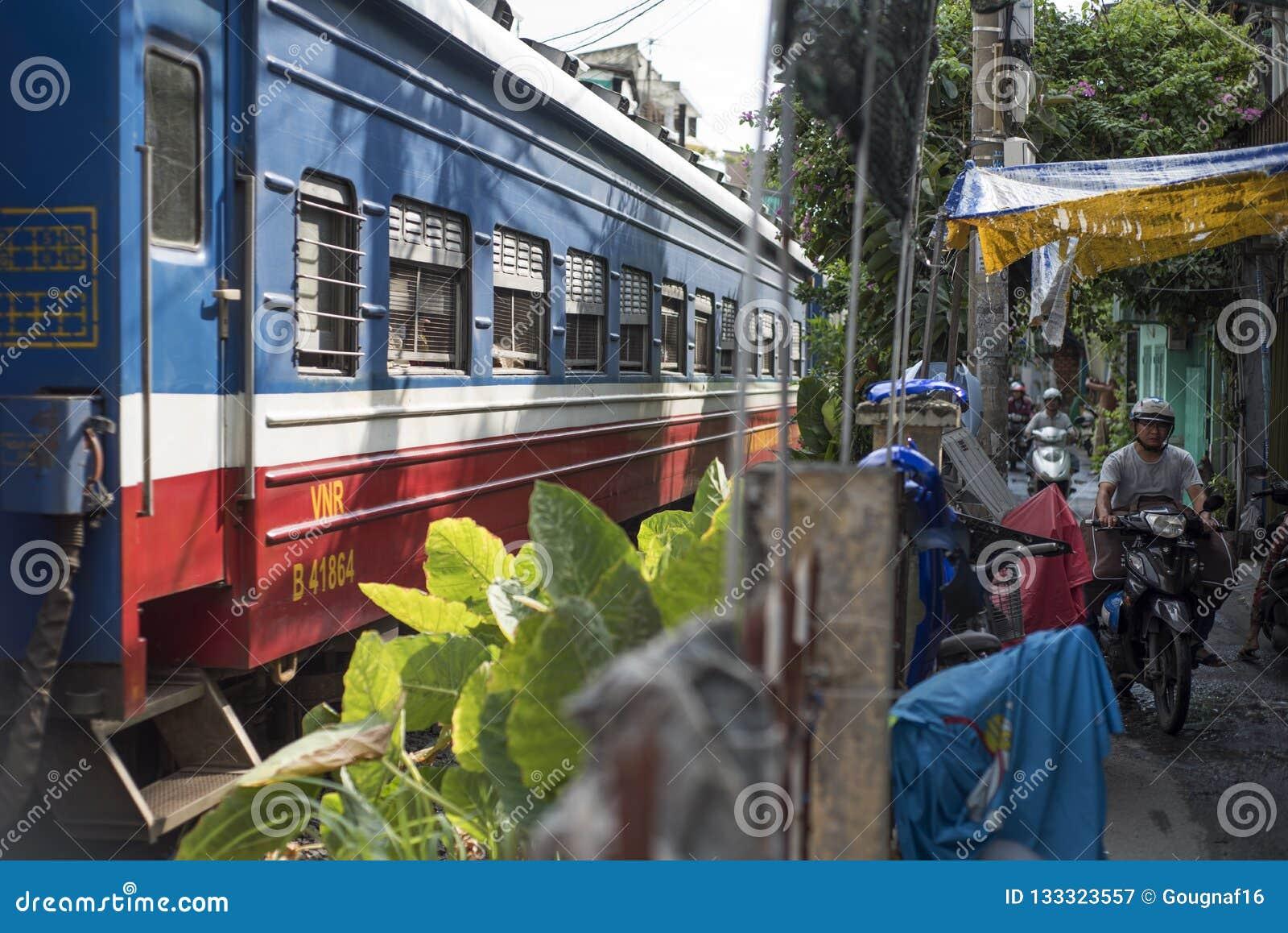 Een trein gaat door een uiterst kleine weg met autopedden over die in Ho Chi Minh City, Vietnam berijden