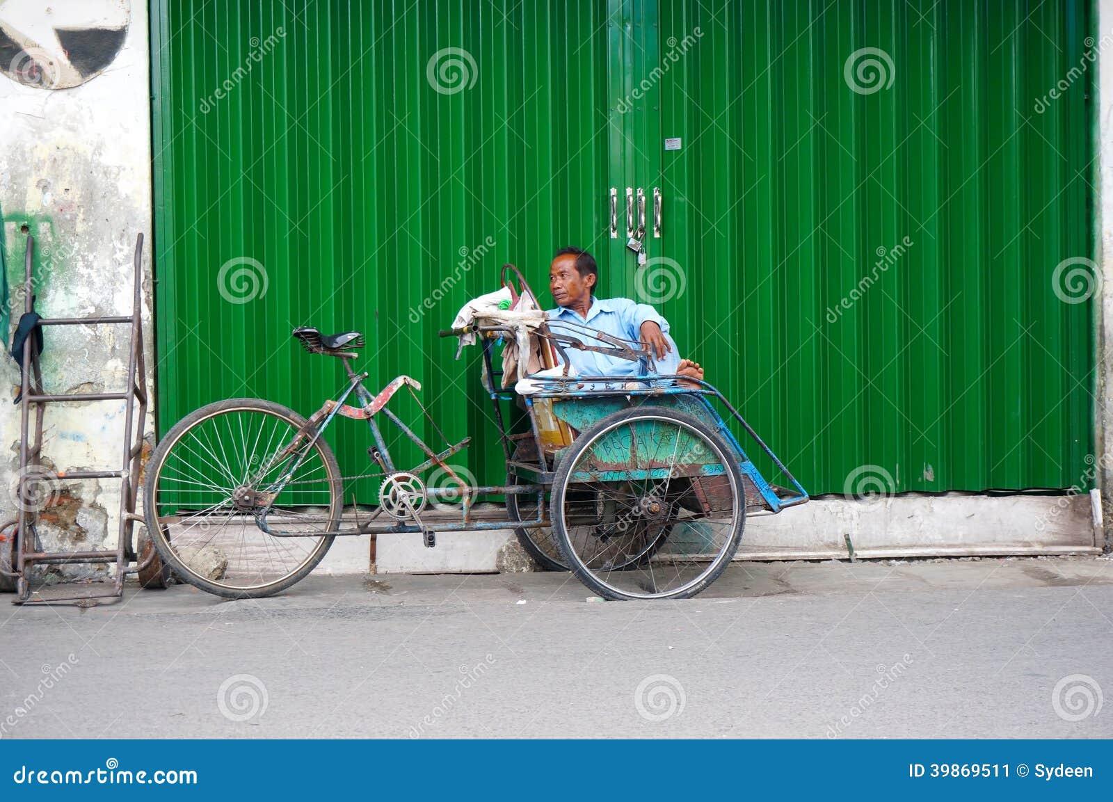 Een trishawruiter rust