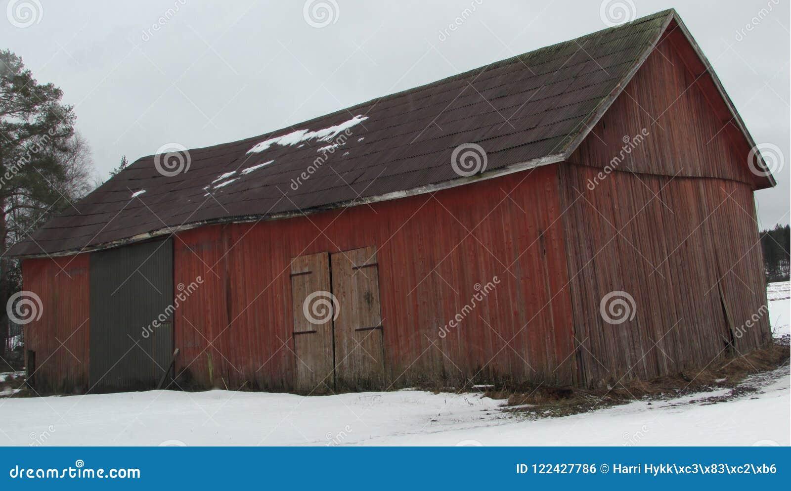 Een typisch Fins gebouw met brede en normale deuren waar de korrel en de landbouwmachines worden opgeslagen