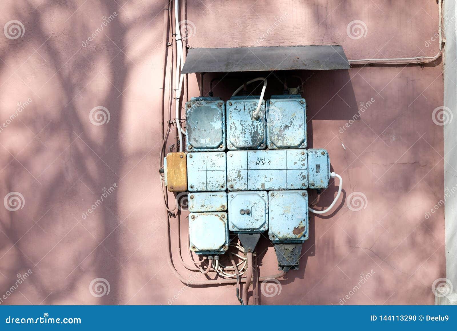 Een uitstekende zekeringkast op een roze muur
