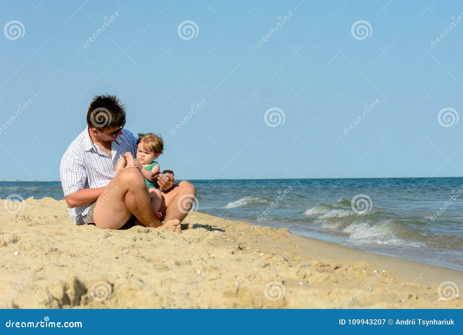 Een vader met een kleine dochter zit op het strand bij de achtergrond van het overzees