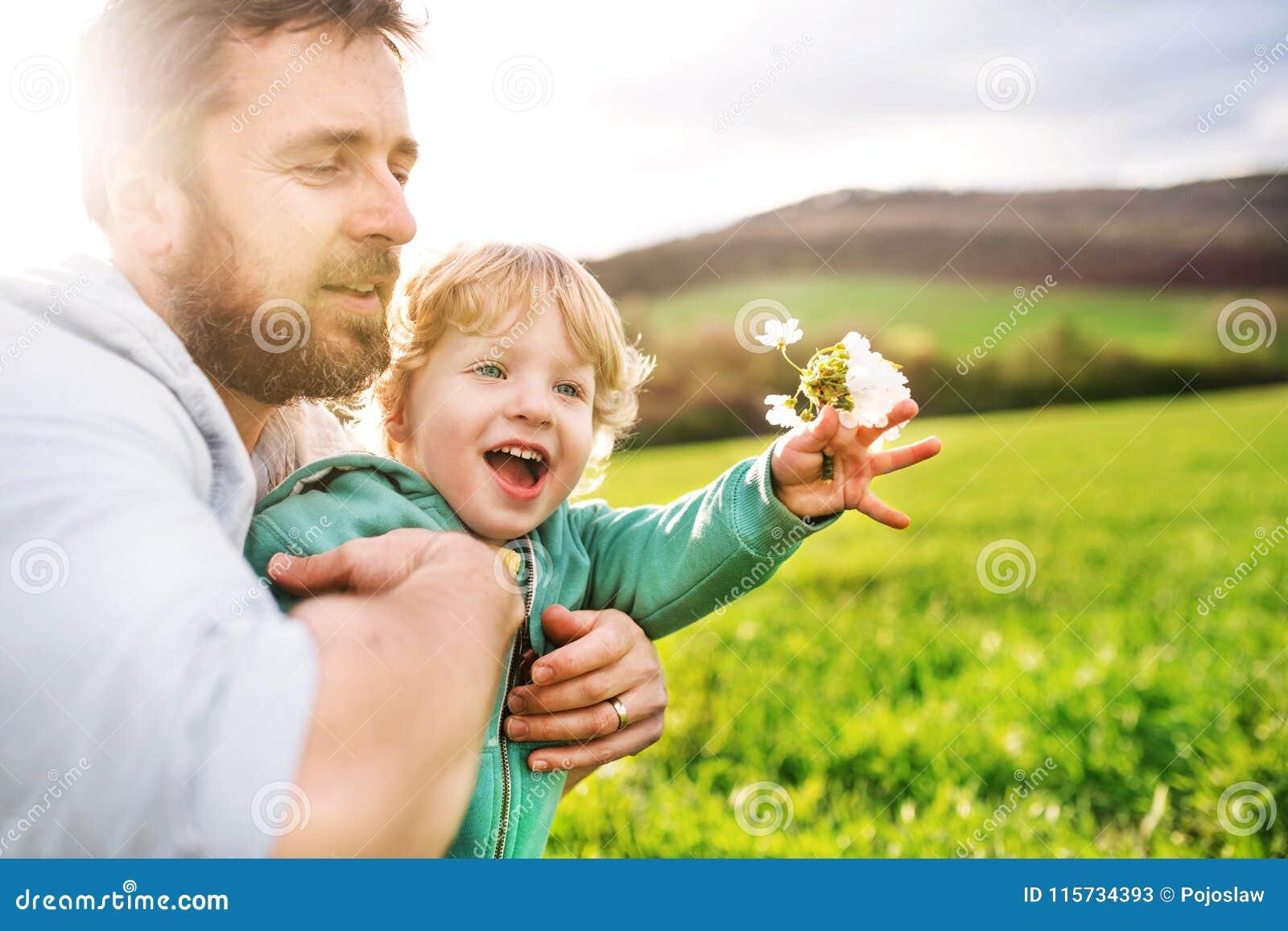 Een vader met zijn peuterzoon buiten in de lenteaard