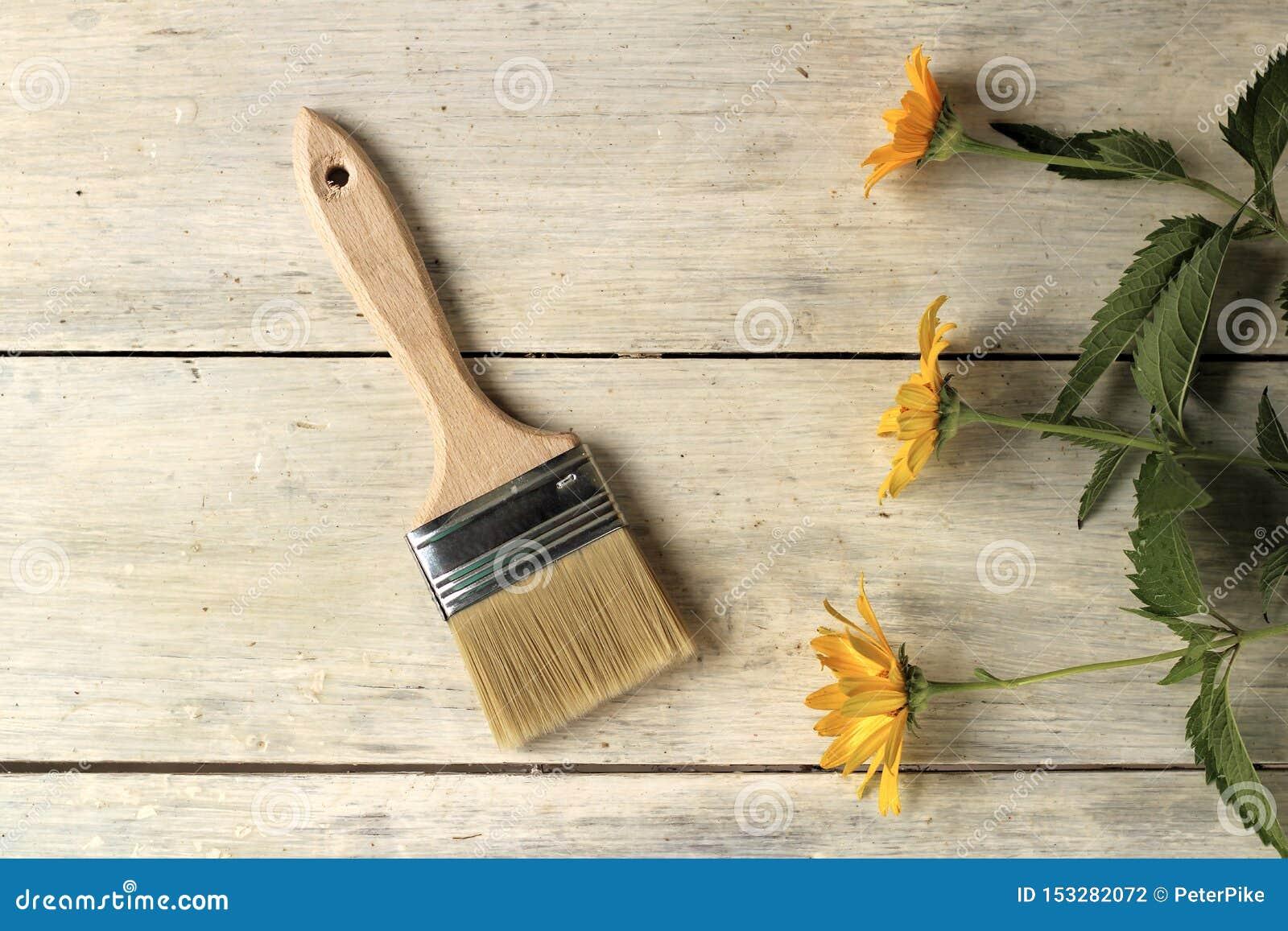 Een verfborstel is naast mooie oranje bloemen op een oude witte uitstekende houten planklijst Plaats voor tekst of embleem