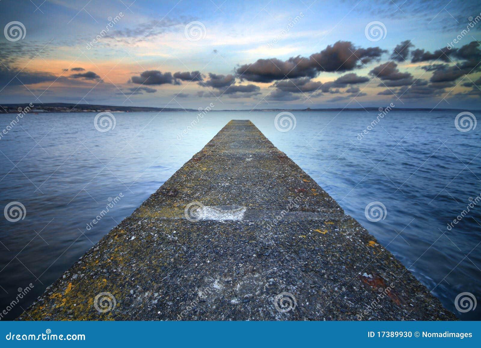 Een verlaten pier die in het overzees wordt uitgerekt.