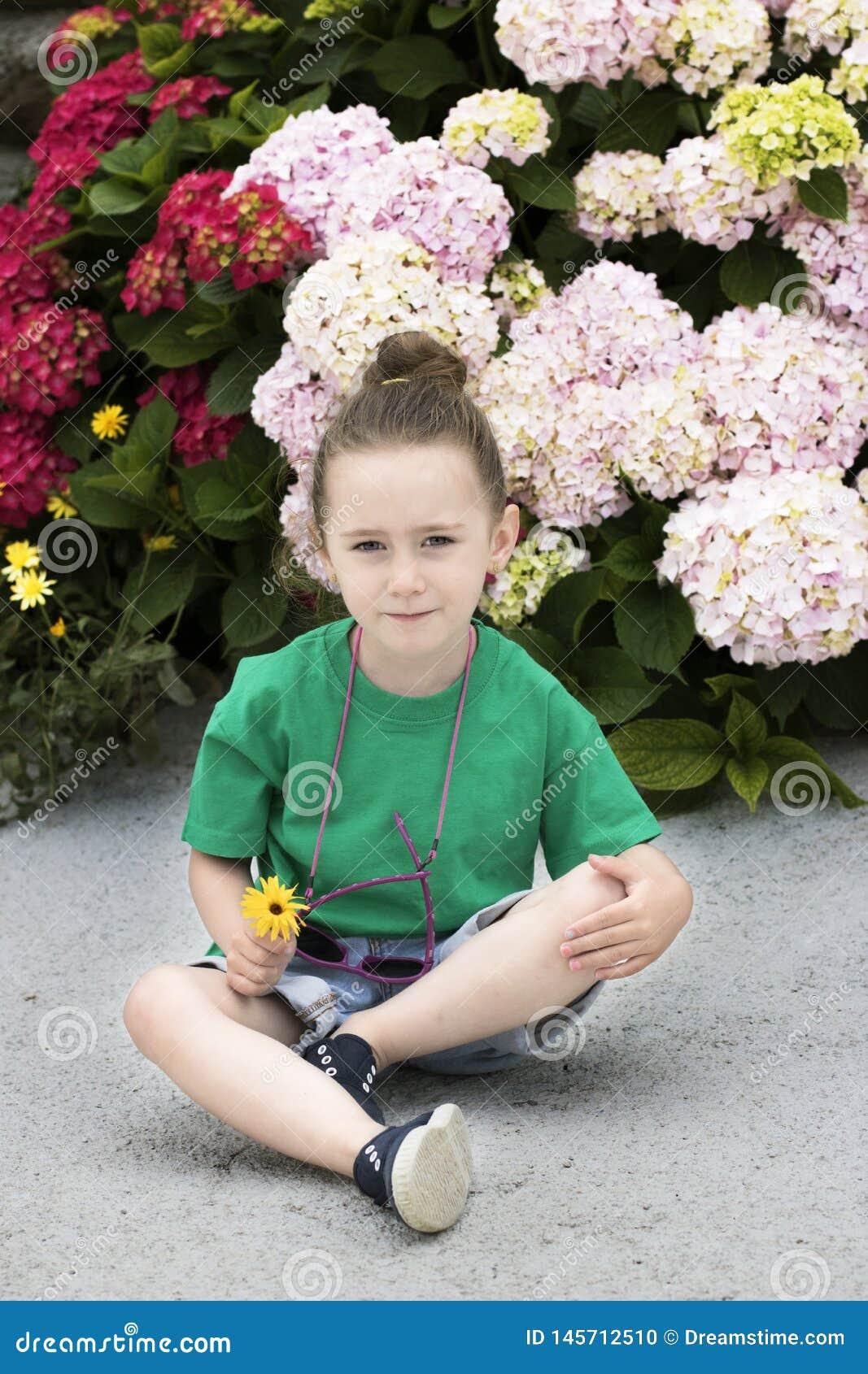 Een vier-jaar-oud meisje voor verscheidene bloeiende installaties