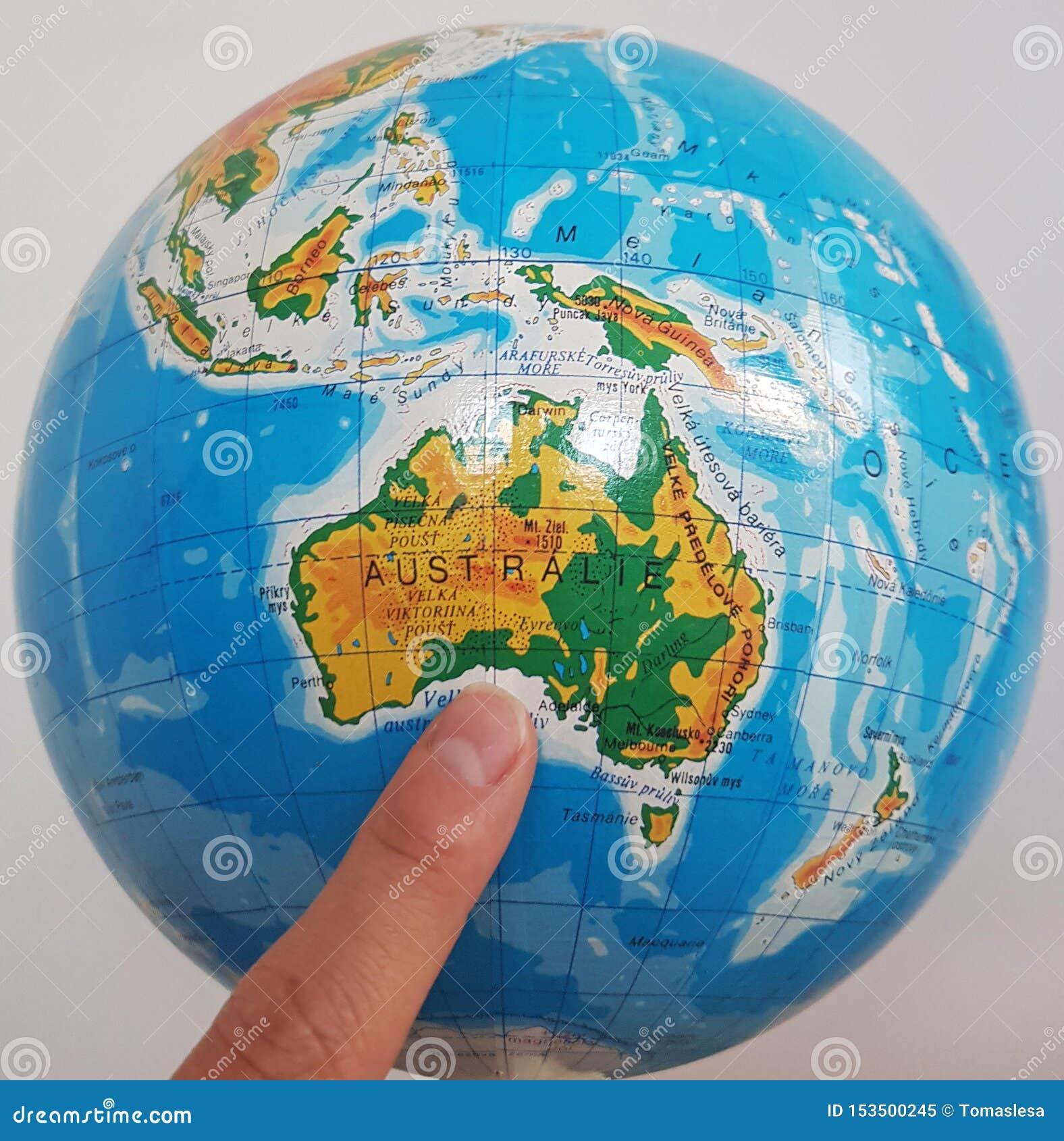 Een vinger die in Australië op een bol richten