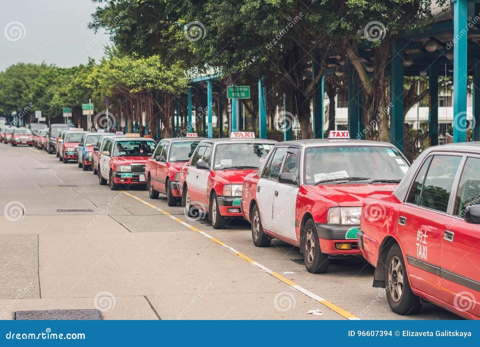 Een vloot van Hong Kong-taxis die bij een taxistandplaats wachten Hong Kong-taxis zijn gemakkelijk herkenbaar door hun rode en wi