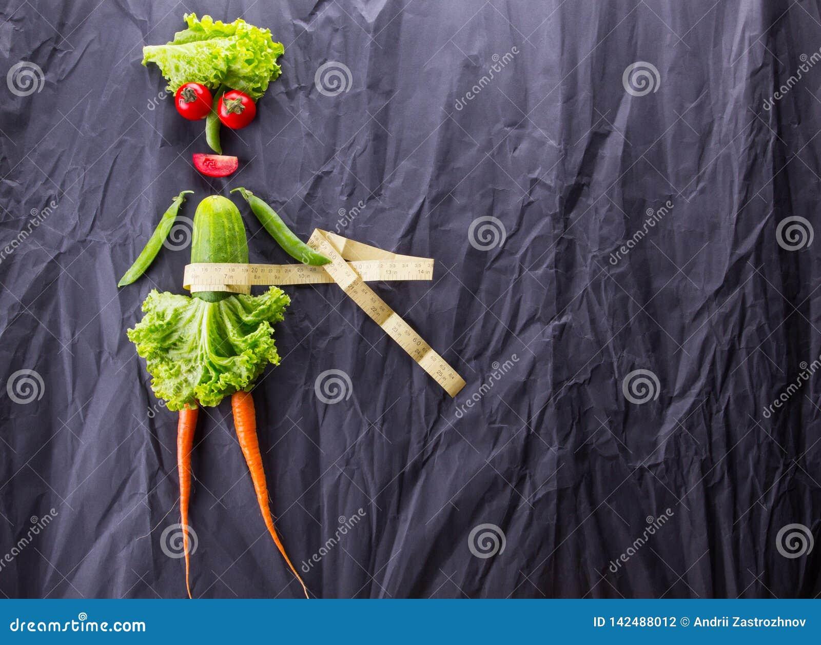 Een voedselconcept het meisje met groenten op zwarte document achtergrond Gewichtsverlies en gezonde levensstijl Met ruimte voor