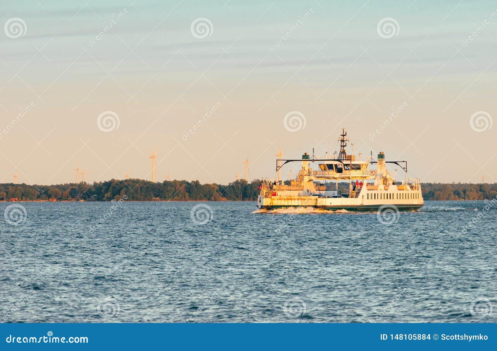 Een voertuigveerboot kruist open water bij zonsondergang