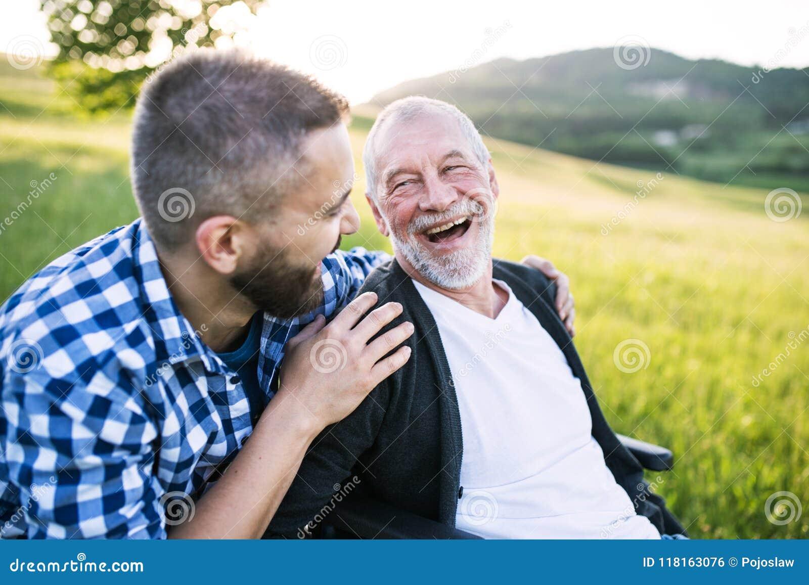Een volwassen hipsterzoon met hogere vader in rolstoel op een gang in aard bij zonsondergang, het lachen