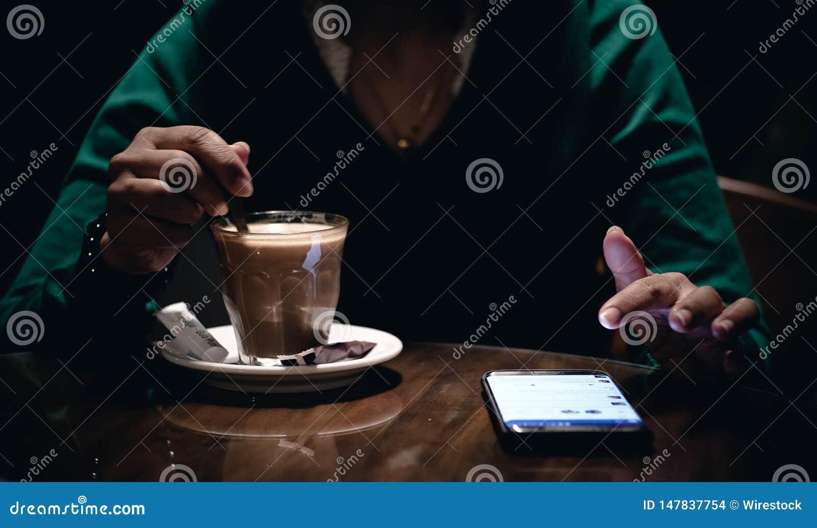 Een volwassen wijfje gebruikend haar telefoon en drinkend koffie in een donkere ruimte