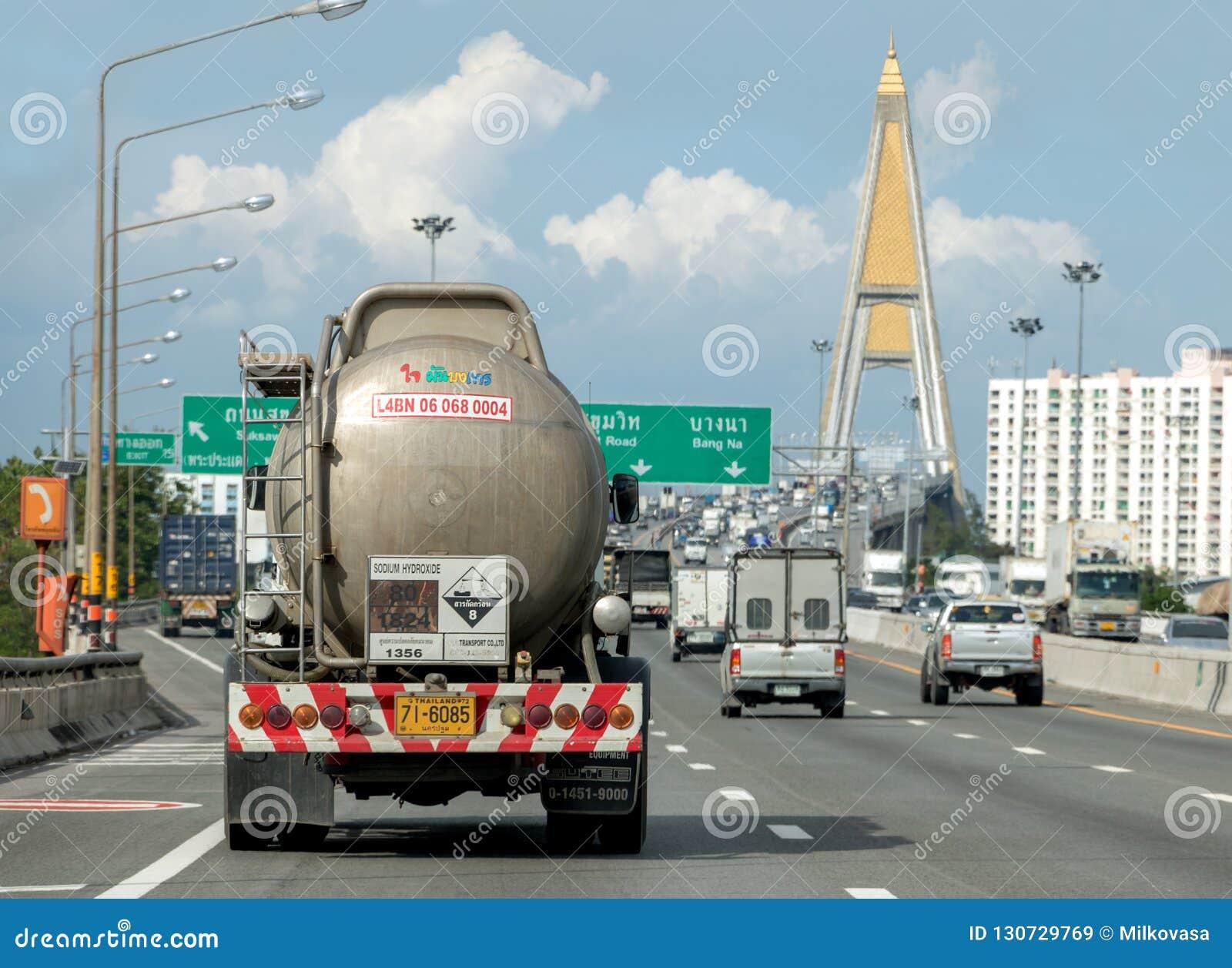 Een vrachtwagen met een tankrit op de weg aan de brug