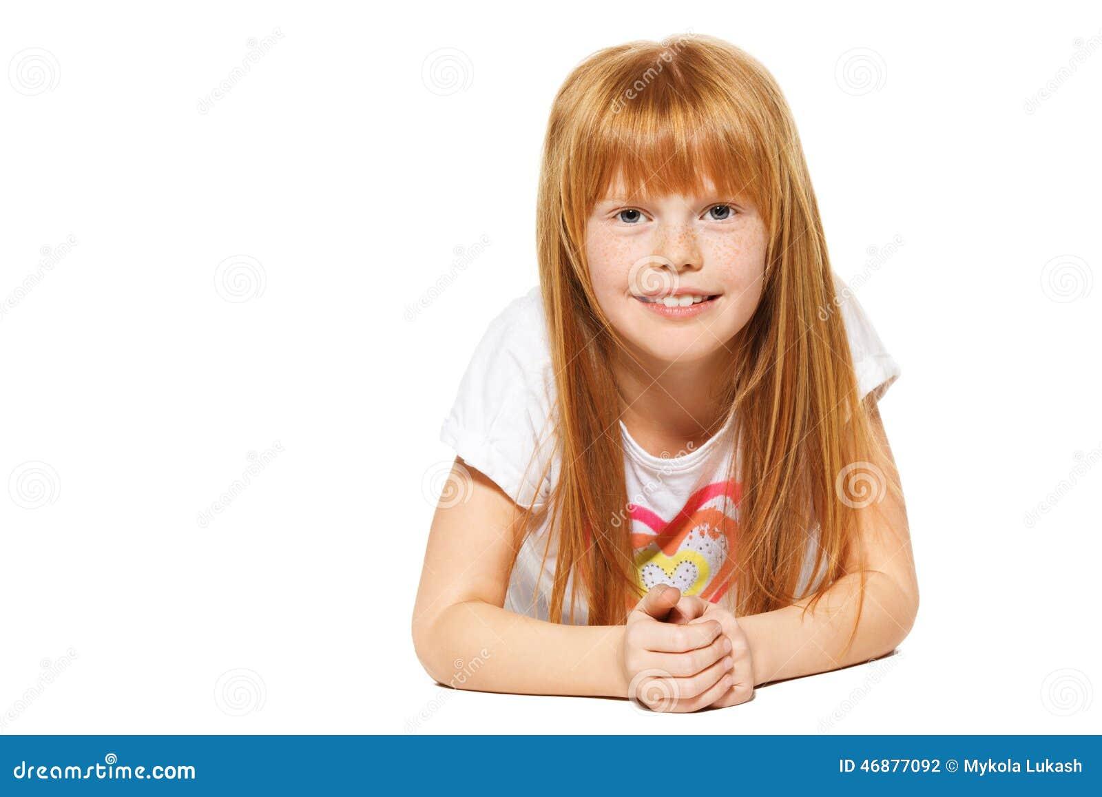 Een vrolijk meisje met rood haar ligt; geïsoleerd op het wit