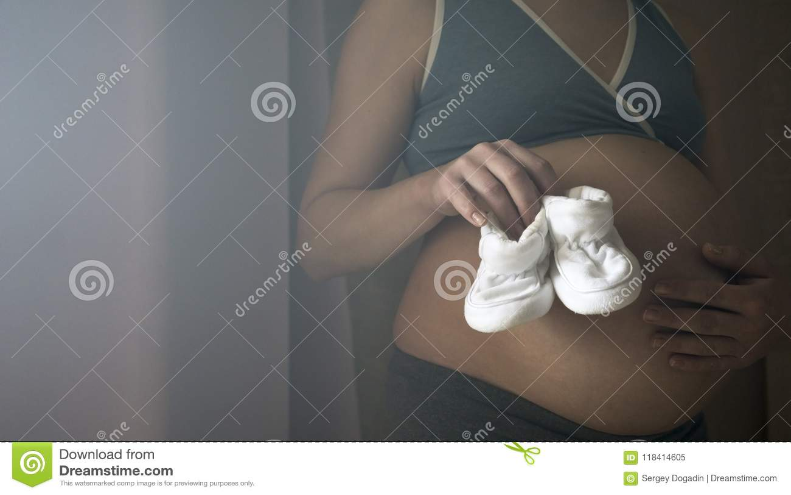 Een vrouw bij de 9de maand van zwangerschap houdt in haar handpantoffels voor een pasgeboren baby