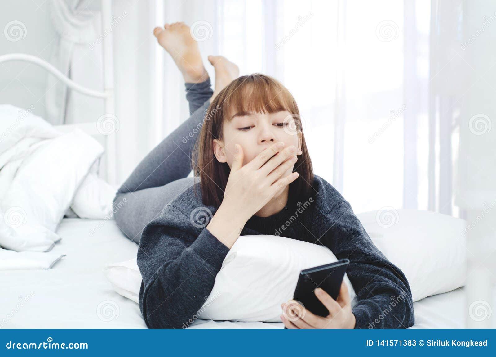 Een vrouw die een zwarte kleding dragen rust in haar ruimte En zij speelt mobiel