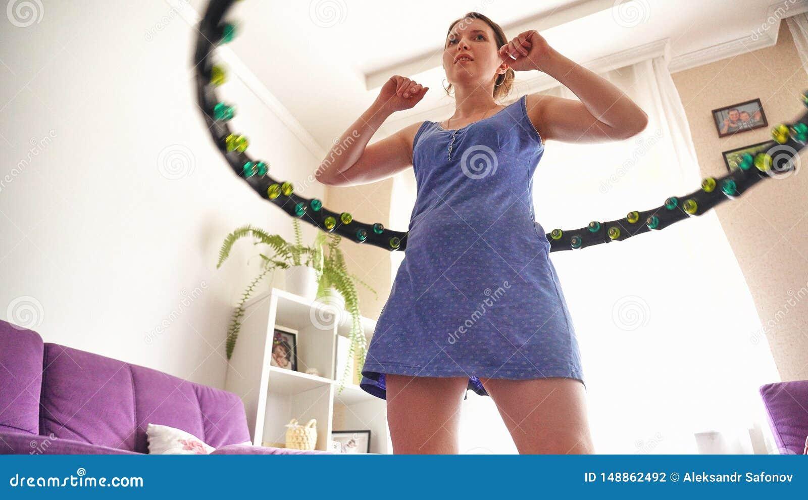 Een vrouw draait thuis een hulahoepel zelf-opleidt met een Hoepel