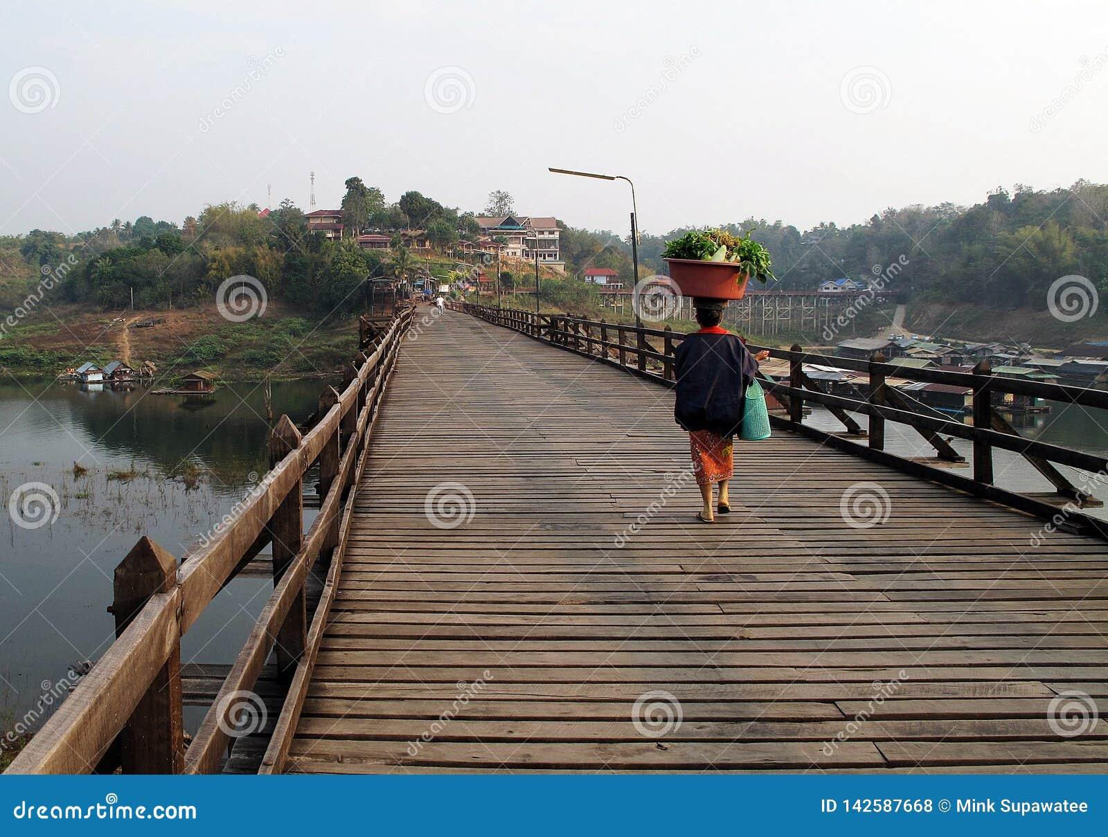 Een vrouw het dragen goed op haar hoofd terwijl het lopen over een houten brug