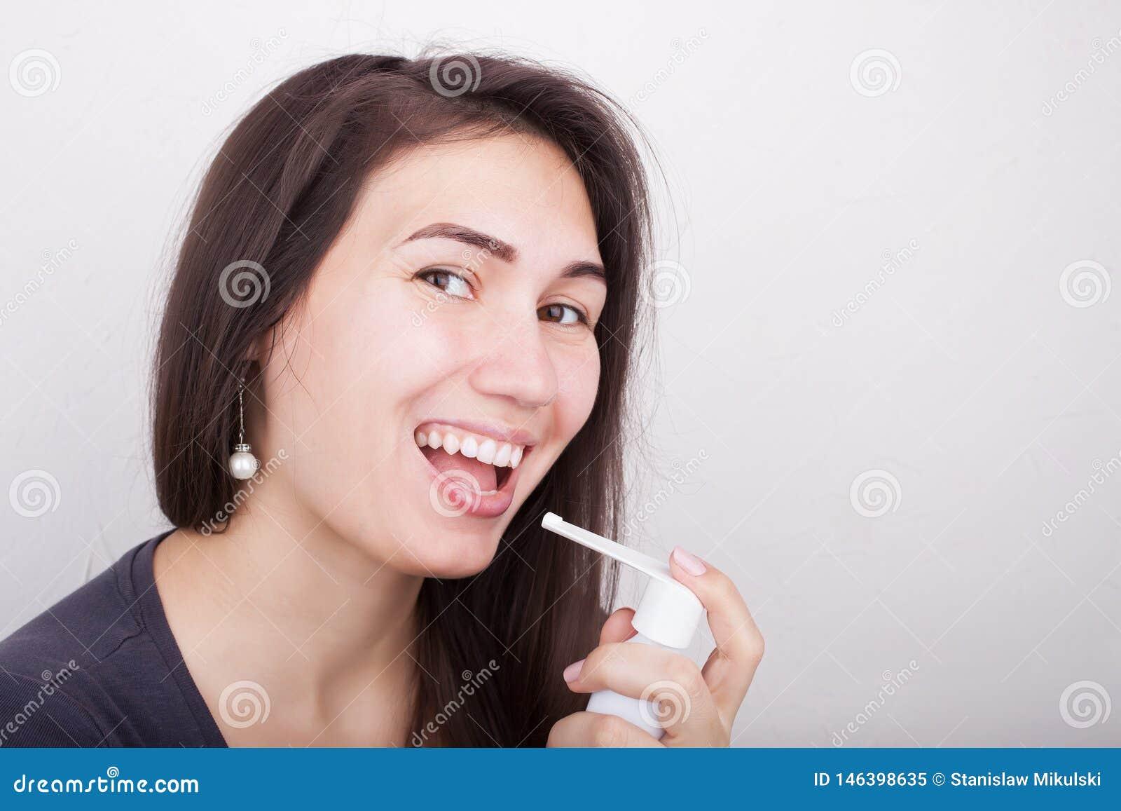 Een vrouw houdt een nevel voor keelgeneeskunde
