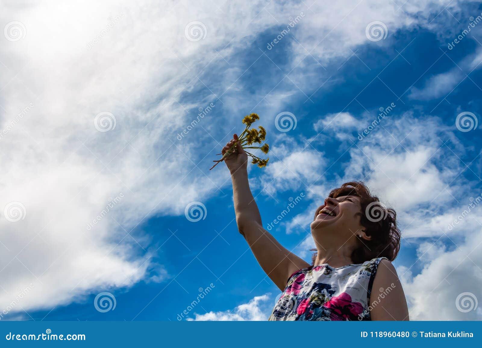 Een vrouw in een katoenen kleding houdt paardebloemen en lacht