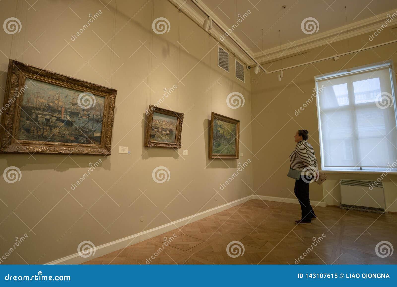 Een vrouw let op de schilderijen