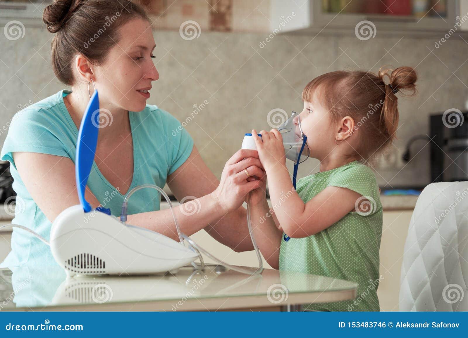 Een vrouw maakt tot inhalatie thuis aan een kind brengt het verstuiversmasker aan zijn gezicht inhaleert de damp van het medicijn