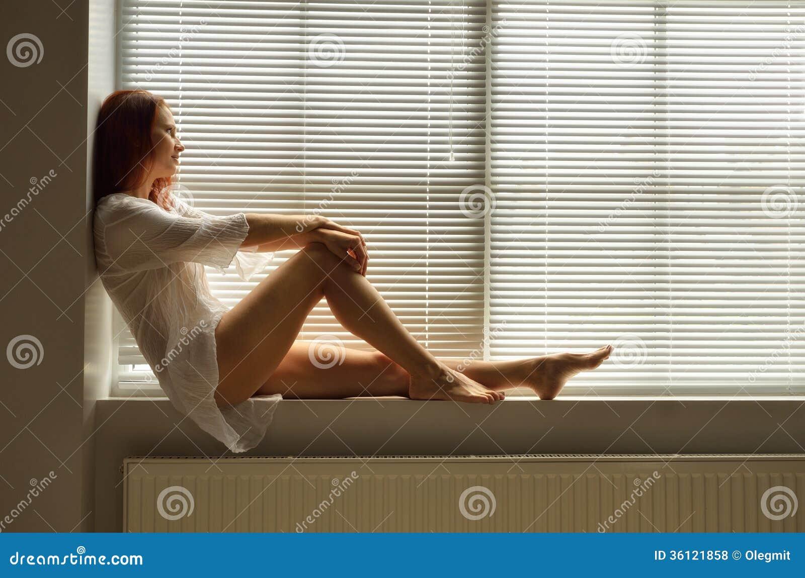 Een vrouw op de vensterbank thuis