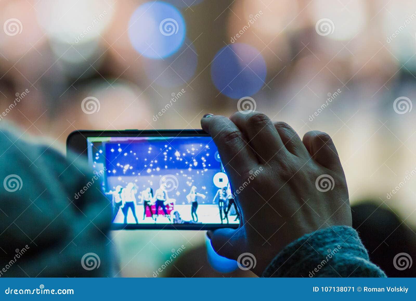 Een vrouw registreert een video of fotografeert de prestaties van kunstenaars op stadium gebruikend haar telefoon Handclose-up on