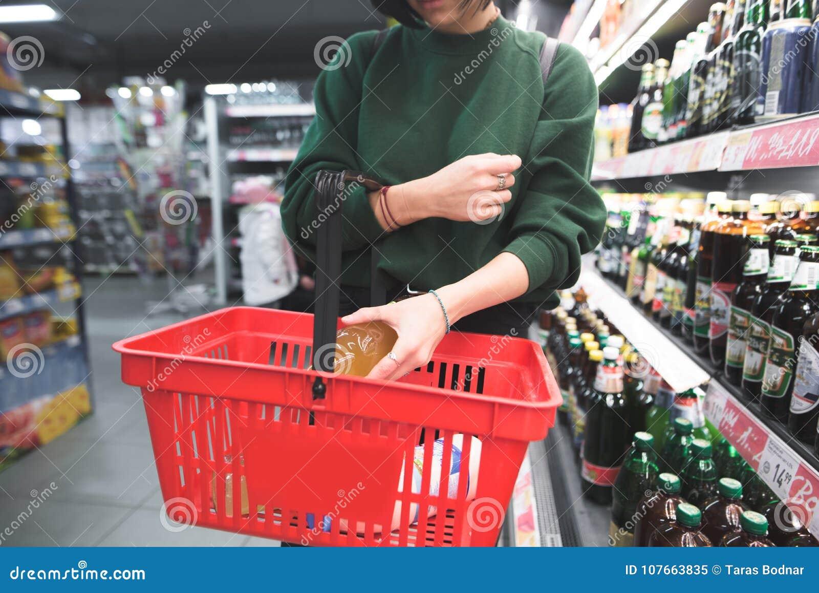 Een vrouw zet een fles alcohol in een rood boodschappenwagentje Het meisje zet een aankoop in de mand