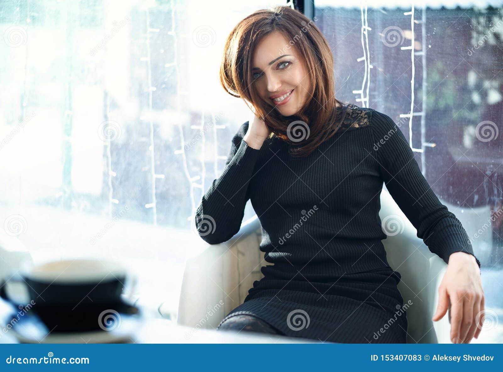 Een vrouw zit in een koffie Close-up, die de camera bekijken