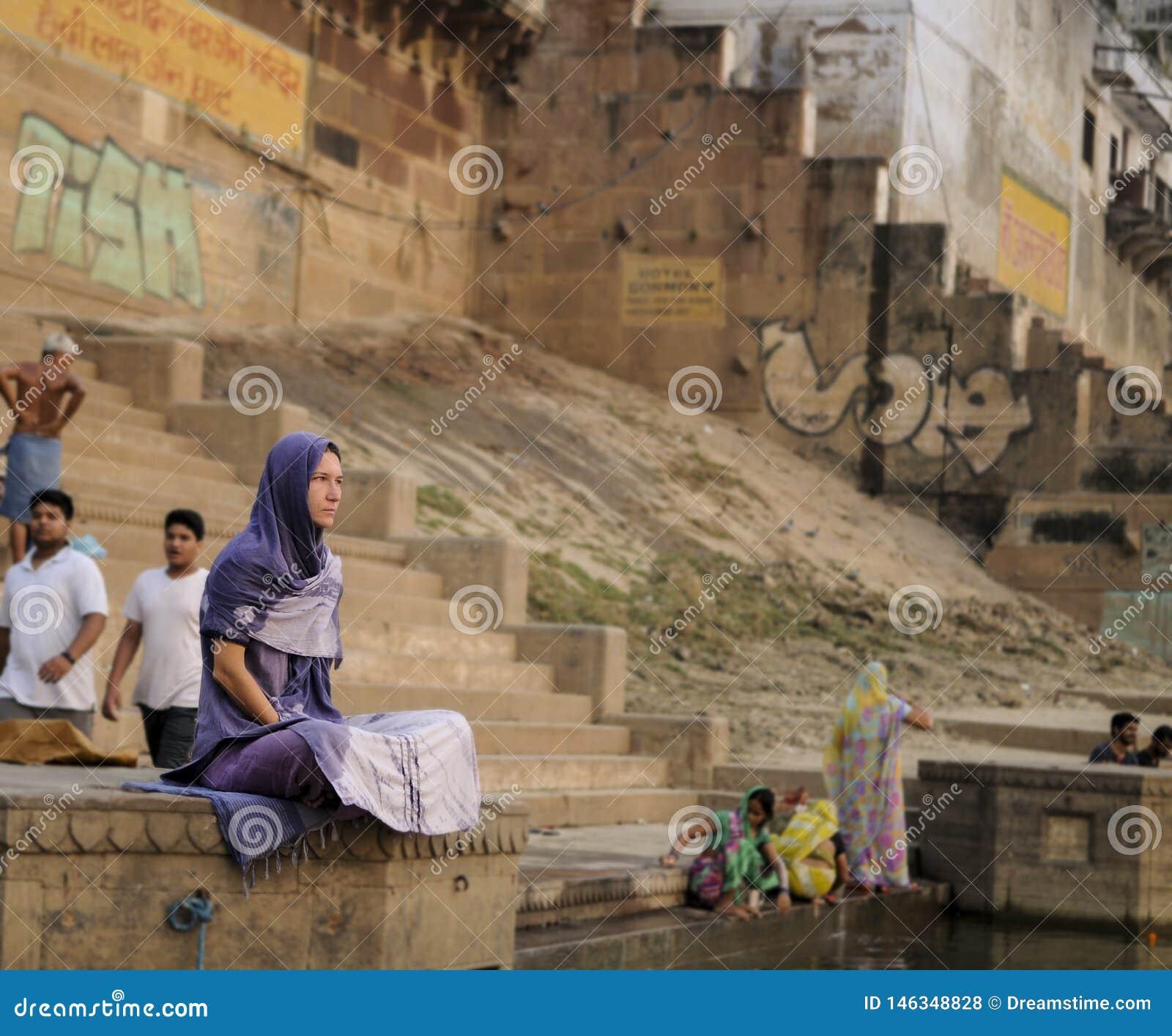 Een vrouw zit stil in de Ganges in de vroege ochtend
