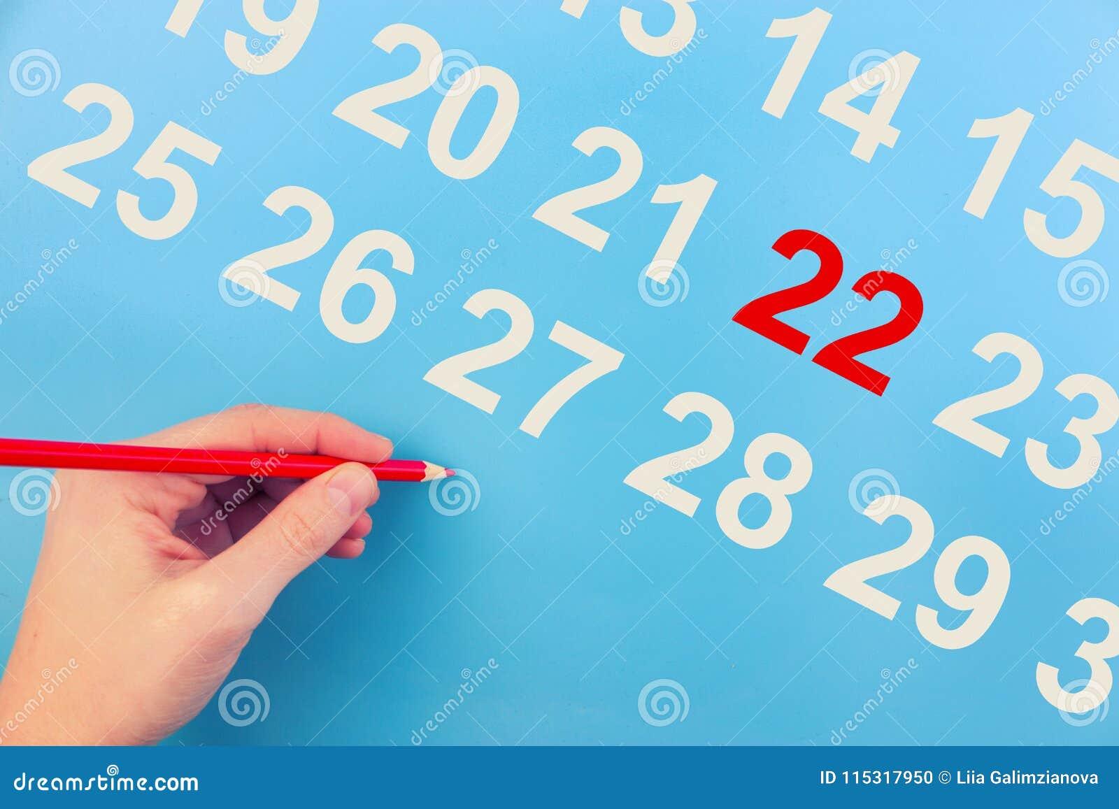Een vrouwelijke hand die de datum omcirkelen