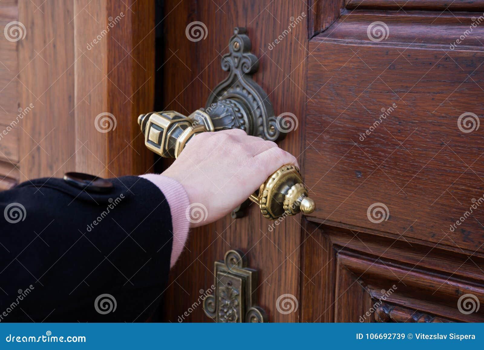 Een vrouwelijke hand die een krukas van een oude houten deur houden