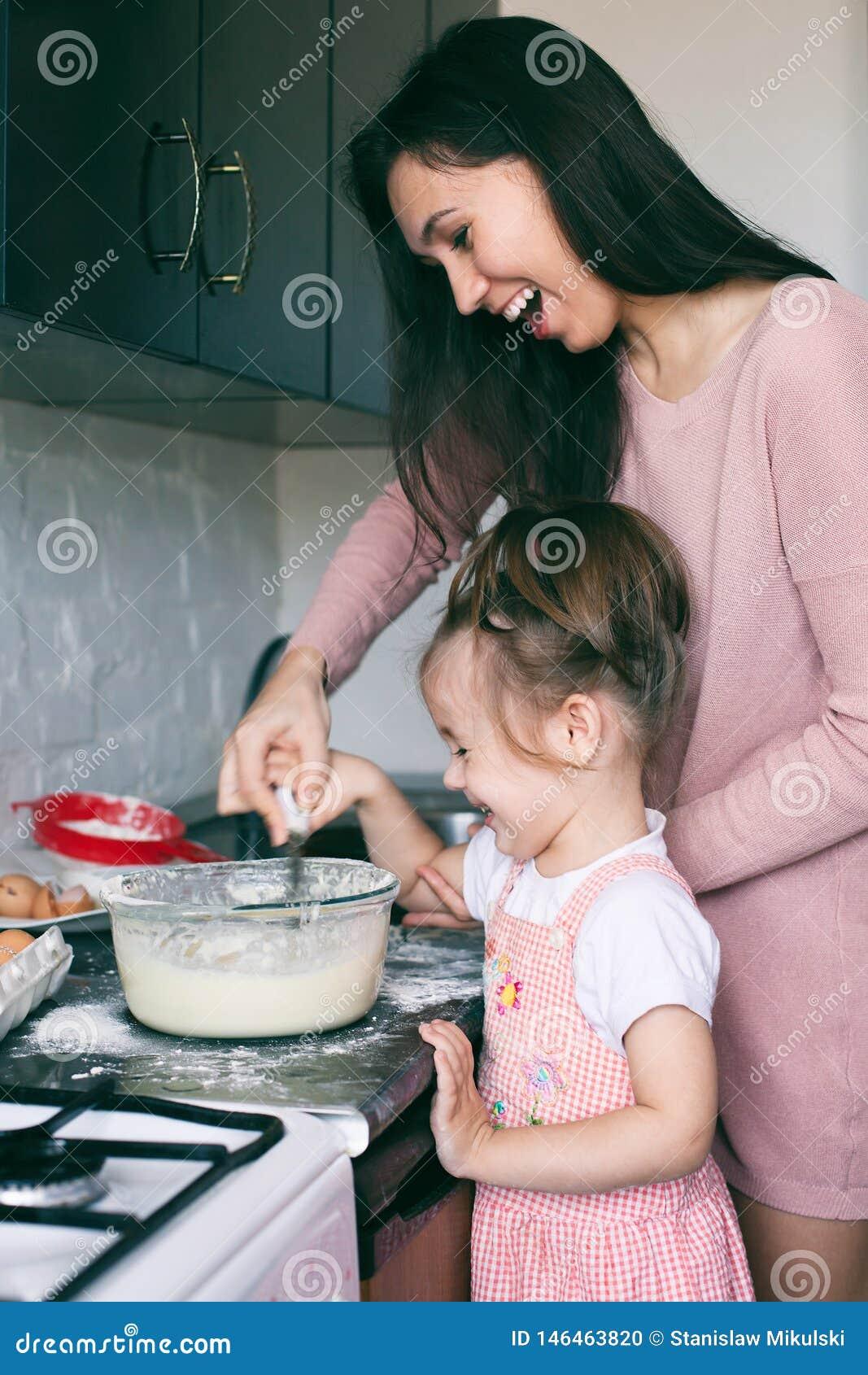 Een weinig leuk meisje en haar moeder die het deeg in de keuken thuis voorbereiden