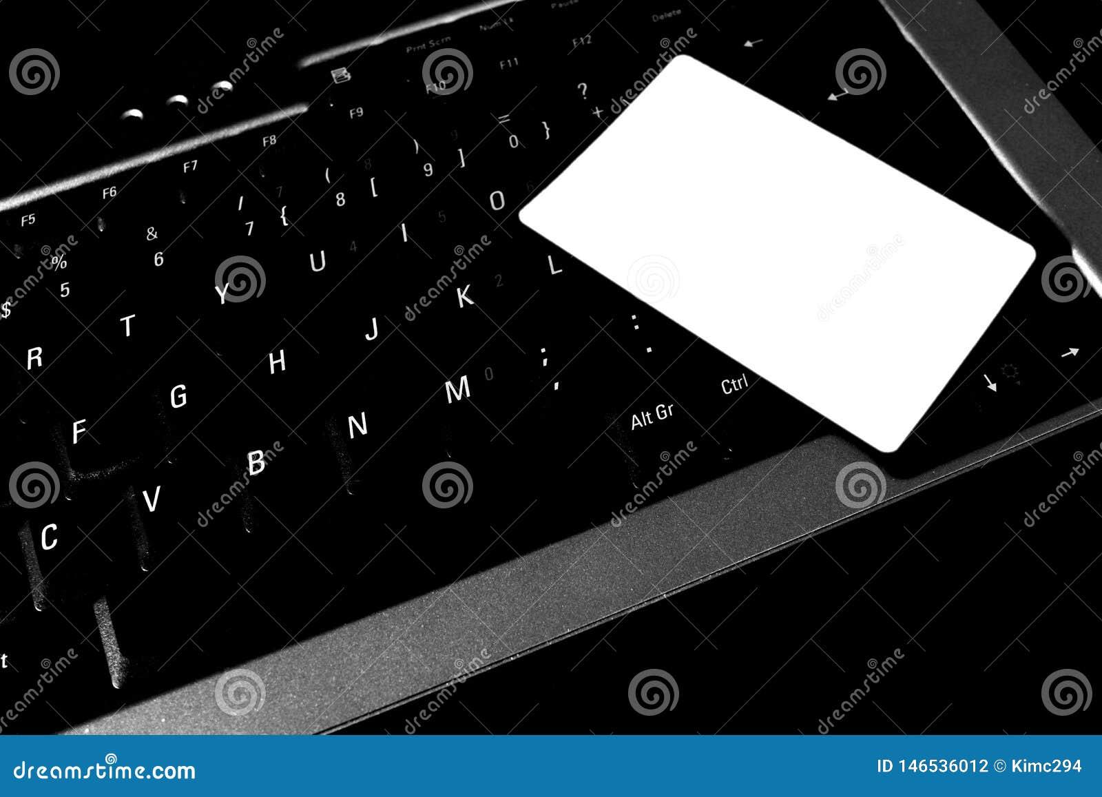 Een witte lege speelkaart ligt op een laptop toetsenbord
