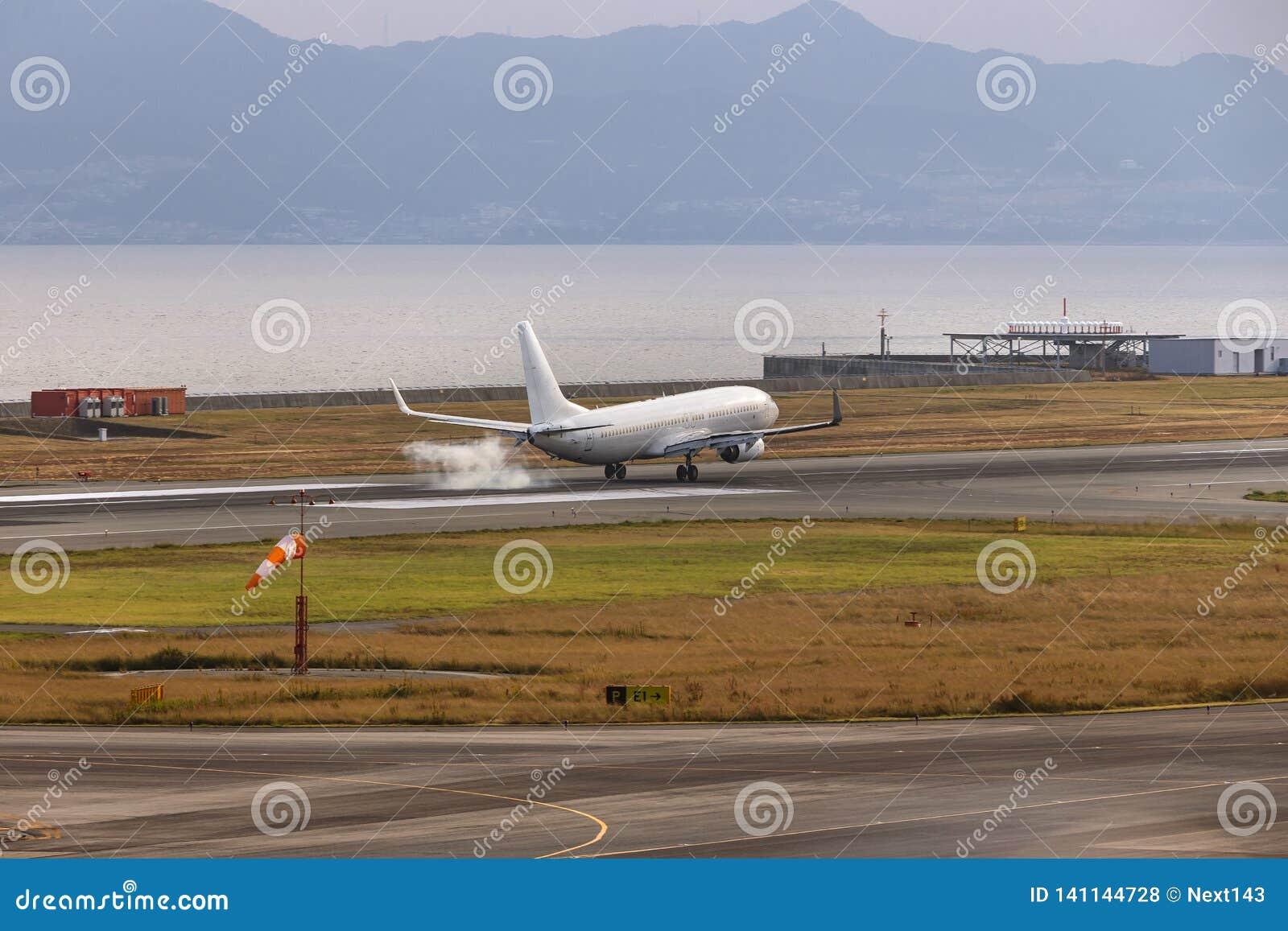 Een witte vliegtuig het landen aanraking neer bij de luchthaven van Osaka, Japan