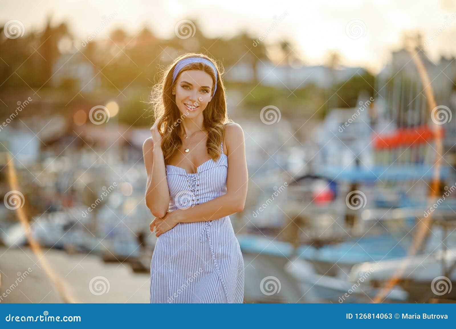 Een zeer mooi sensueel en sexy meisje in een blauwe gestreepte kleding i