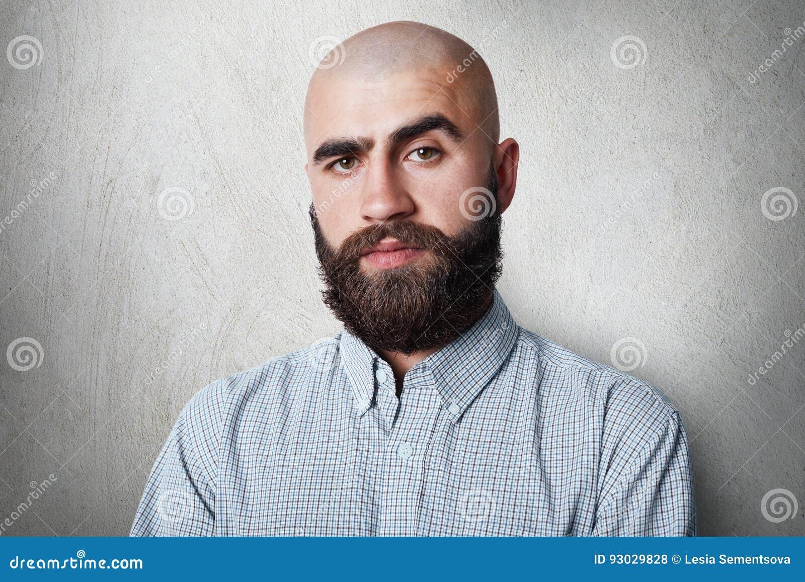 Een zeker kaal mannetje met dikke zwarte wenkbrauwen en baard die gecontroleerd overhemd dragen die het sombere uitdrukking stell