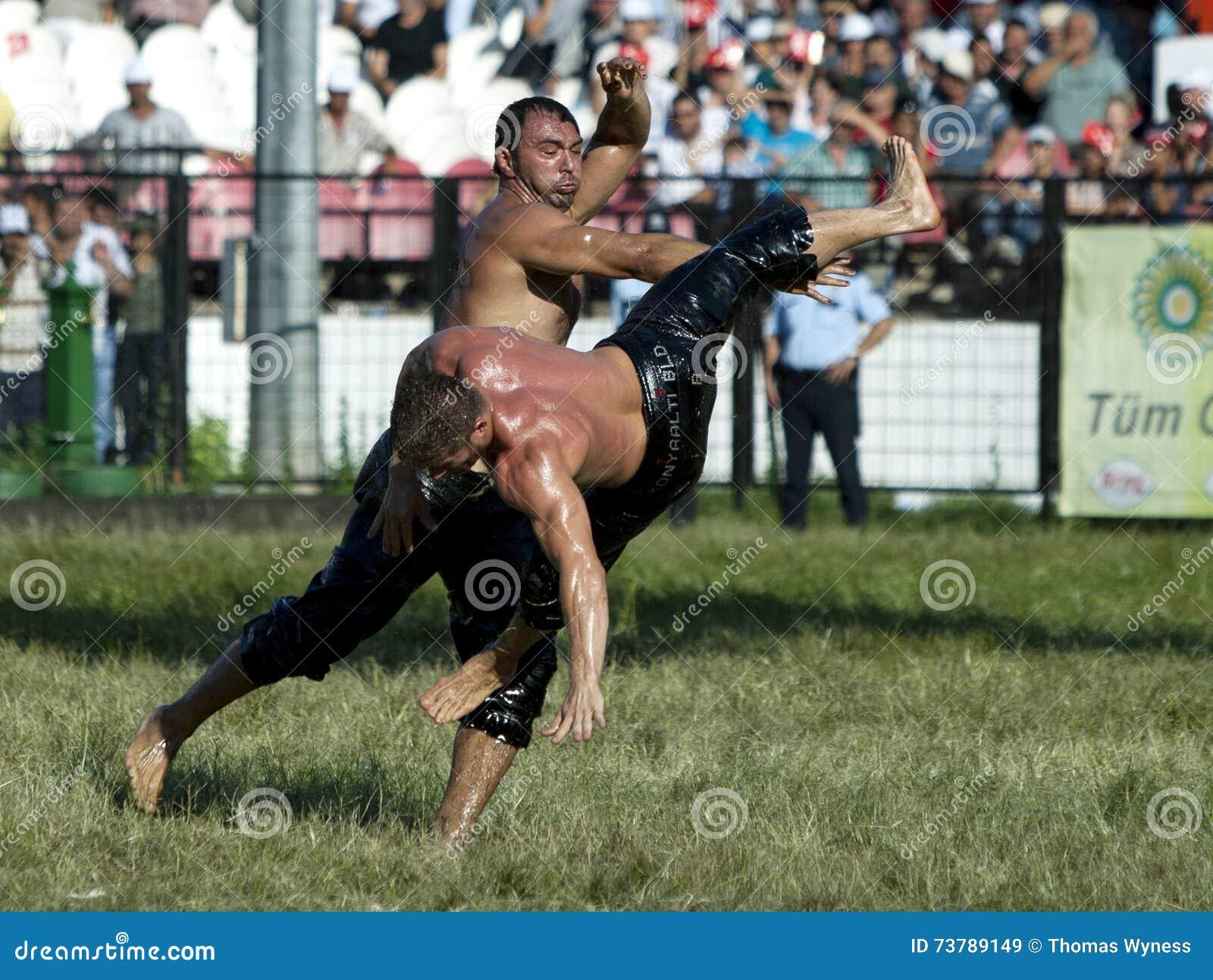 Een zwaargewicht worstelaar wordt geworpen in de lucht door zijn tegenstander bij het de Olie van Kirkpinar Turkse het Worstelen